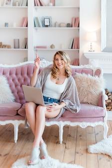 Портрет великолепная блондинка с ноутбуком, работающих на дому. красивая женщина фрилансера, говорить в видео конференции онлайн с ноутбуком. женщина работает на компьютере, фрилансере или блоггере.