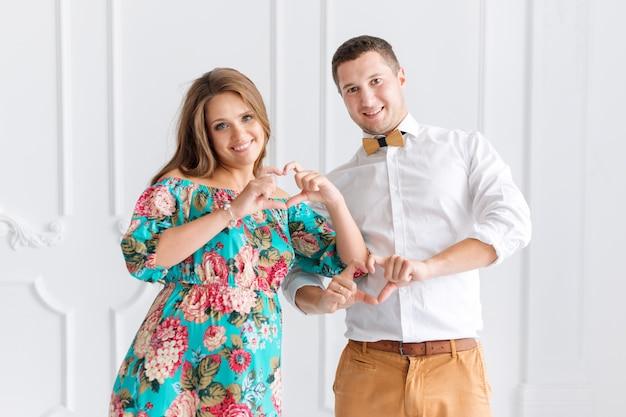 Красивая беременная пара счастлива вместе, ожидая ребенка. мужчина и женщина в белом минималистском интерьере, показывая сердца руками. сосредоточиться на пальцах. поделитесь любовной концепцией.