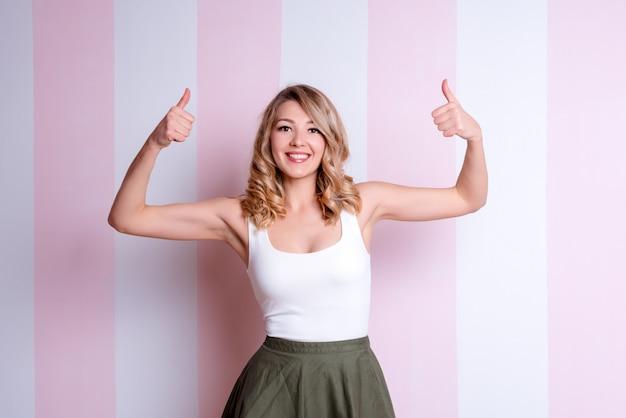 Счастливая эмоциональная женщина представляя и показывая большие пальцы руки вверх на розовой предпосылке. молодая белокурая женщина давая большие пальцы руки вверх, одобряющ делать положительный жест с рукой для успеха. смотря на камера, жест победителя