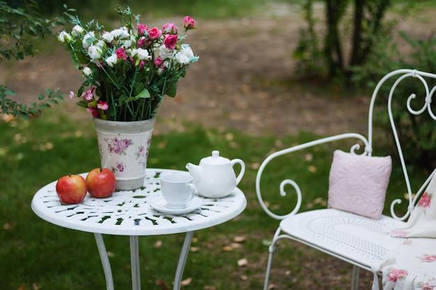 Белый фарфор установленный для чая или кофе на таблице в саде над нерезкостью зеленеет природу. летняя вечеринка.
