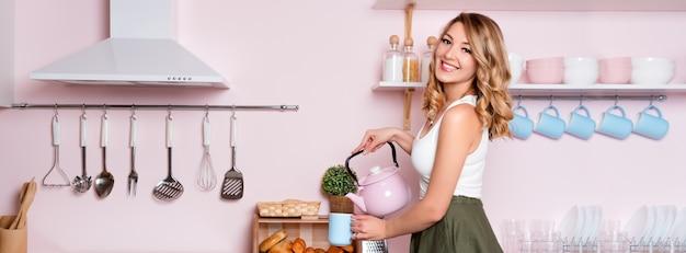 キッチンで自宅でコーヒーやお茶を作る若い幸せな女。事務所に行く前に彼女の朝食を持っている金髪の美しい少女。コーヒーブレイク。ピンクとブルーのパステル調のモダンなキッチンインテリア