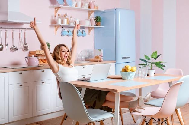 Усмехаясь молодая женщина используя компьтер-книжку в кухне дома. блондинка работает на компьютере, фрилансер или блоггер, работая на дому