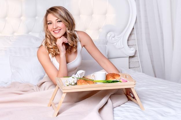 朝はベッドで朝食を持っている若いブロンドの女性。ホテルの寝室のトレイでおいしい朝食