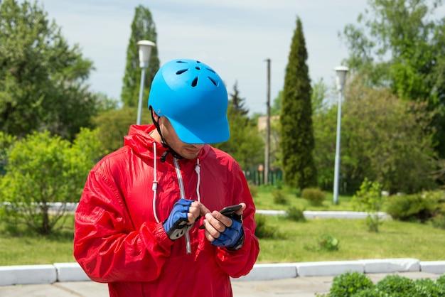 サイクリストがスマートフォンでナビゲートしている、または携帯電話でテキストメッセージを送信している