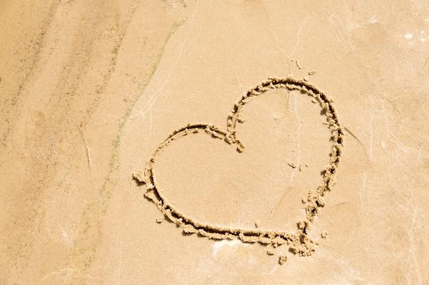 Форма сердца нарисована в песке на пляже