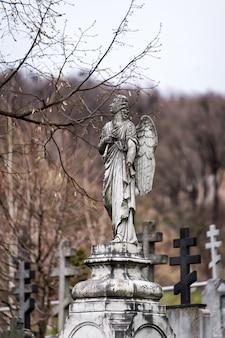 Старая надгробная скульптура ангела со сломанной рукой и крыльями на кладбище