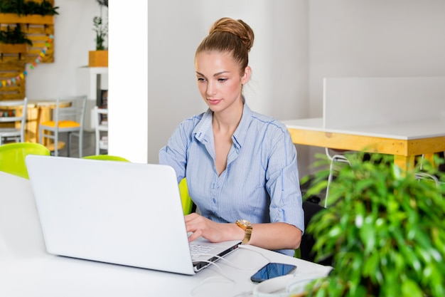 ビジネス、技術、グリーンオフィスコンセプト-オフィスでラップトップコンピューターを持つ若い成功した実業家。タブレットコンピューターを使用しての女性。