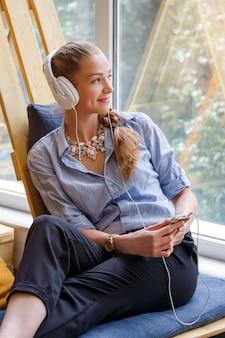 Милая коммерсантка слушает к музыке в современной просторной квартире. внештатная работа, отдых и концепция отдыха. женщина в бизнесе. фрилансер в коворкинг-центре отдыхает.