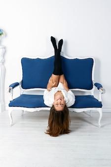白のインテリアで青いソファに横たわっているセクシーな若い女性。