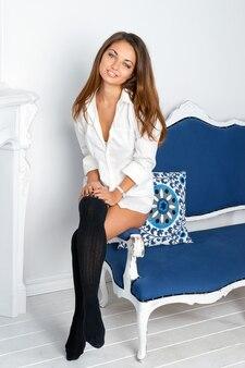 白のインテリアで青いソファに座っているセクシーな若い女性。