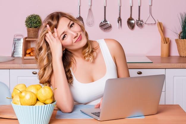 Взволнованный и грустный студент женского пола, ищущий информацию в ноутбуке онлайн, сидящем в кухне.