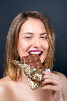 チョコレート・バーを食べる明るい化粧品で美しい裸の若いブロンドの女性。