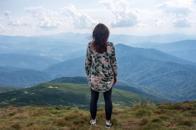 Девушка путешествуя в горах одна, спокойная сцена. прогулка на свежем воздухе, женщина турист на вершине горы. вид сзади на пейзаж. тема странствия. карпаты, вид с горы