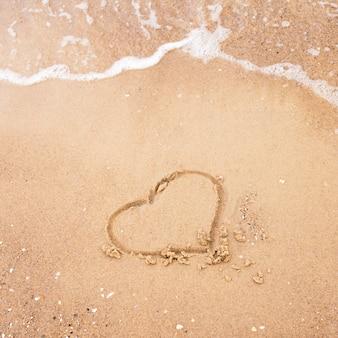 Сердце нарисовано в песке с волной моря