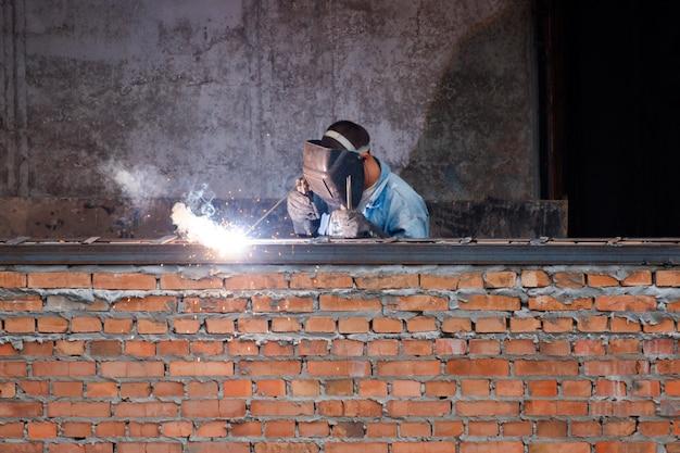 Промышленник сваривает железные детали в новом здании
