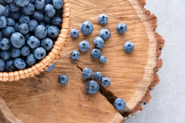 木製のテーブル上のバスケットのブルーベリー。熟したとジューシーな新鮮なブルーベリーのクローズアップ、トップビュー