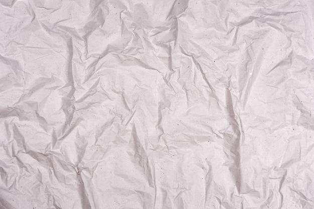 Мятую текстуру серой бумаги. фон морщинистой бумаги с трещинами и изломами.