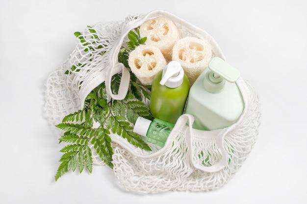ローション、シャンプー、コンディショナー、または液体石鹸をエコバッグに入れたさまざまな容器。ヘチマまたはヘチマの手ぬぐい、野菜スポンジ、プラスチックの代替、廃棄物ゼロ、環境に優しい。