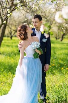 咲く春の庭を受け入れる若いカップル。愛とロマンチックなテーマ。