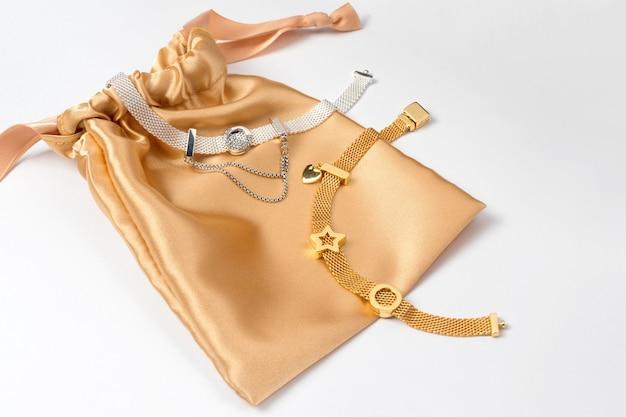 Серебряные и золотые браслеты в золотом шелковом подарочном пакете