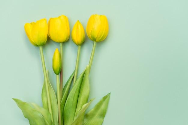 ミントの背景に黄色のチューリップの花の花束