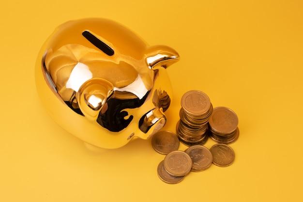 黄色の背景にお金の塔を持つ黄金の貯金箱