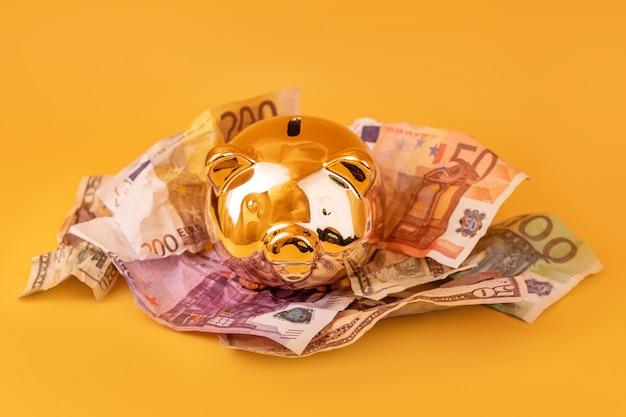 現金お金、ユーロ、ドル紙幣と黄金の貯金箱