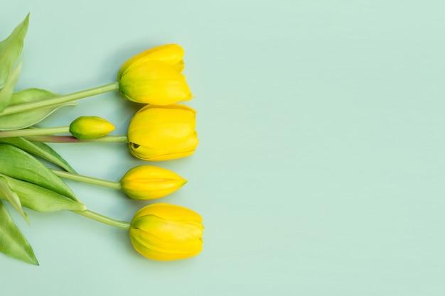 緑のテーブルに黄色のチューリップの花の花束。フラット横たわっていた、トップビュー。最小限の花のコンセプト。春の花