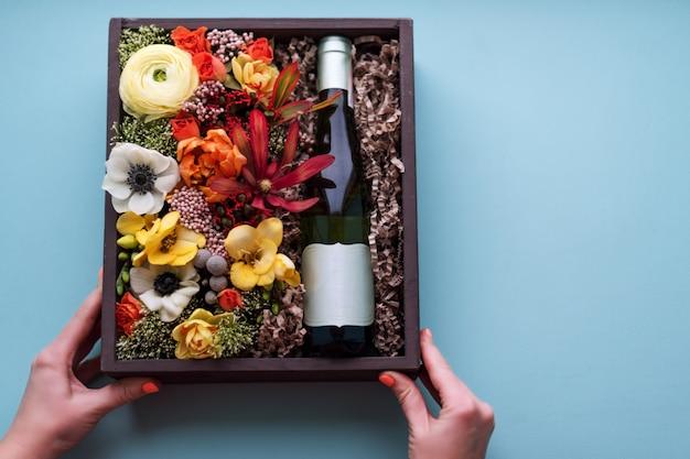 古い木製の素朴なボックスに白ワインのボトルと花の花束を保持している女性手