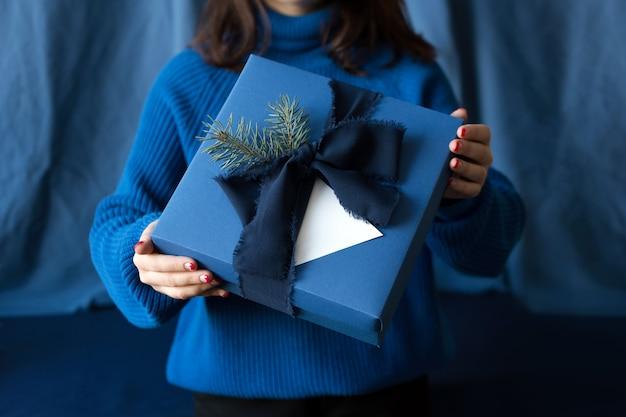 弓で青いボックスにクリスマスギフトを保持している認識できない女性