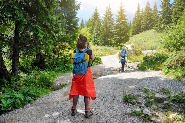 友達が一緒に楽しんで、女性が山でハイキングする彼女の友人の写真を撮る。