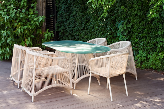 Плетеные кресла и стол, современная садовая мебель.
