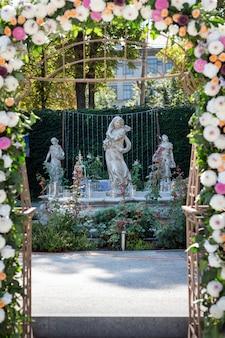 屋外の花を持つ結婚式のアーチ。彫刻と噴水のある庭での結婚式。