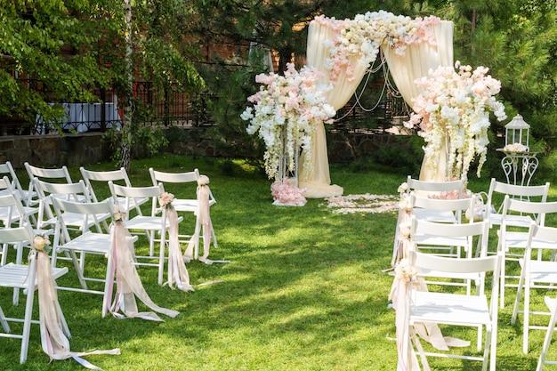 屋外の布と花で飾られた結婚式のアーチ。