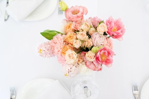 休日や結婚式の夕食のための花のテーブルデコレーション。屋外レストランでの休日の結婚披露宴のテーブル。