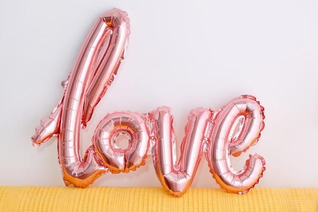 Любовное слово из розового надувного шарика на белом