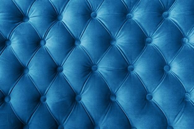 ボタン付きの青い布のソファの質感