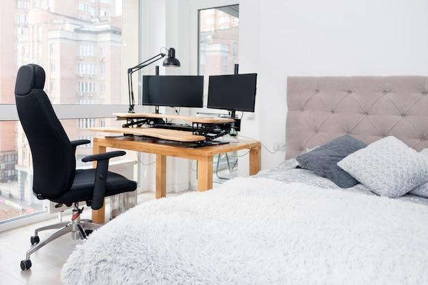 書斎コーナーのある寝室のインテリア。大きなダブルベッド、コンピュータとローリングチェア付きのデスク。
