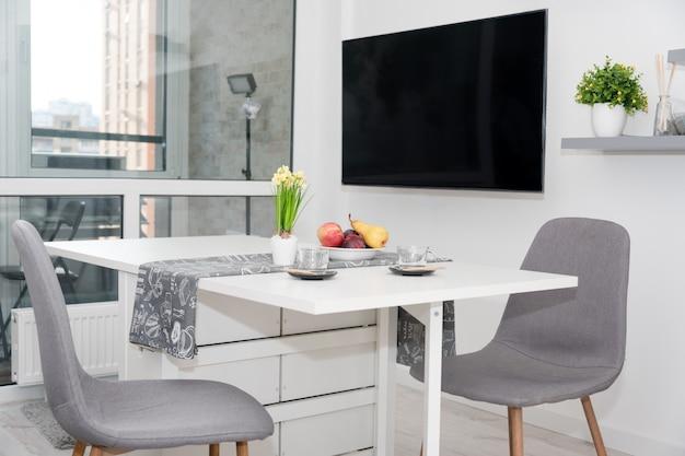 Кофейные чашки и фрукты на завтрак. утренний стол с эспрессо, фруктами и цветами на белом деревянном столе на кухне