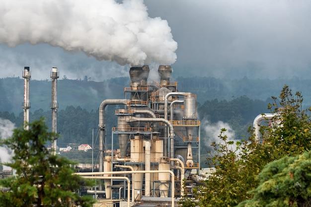 Химический завод с дымовой трубой. выброс дыма из заводских труб.