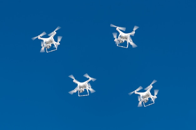 何十ものドローンが青空に群がります。クアッドコプターの無人偵察機とデジタルカメラを空中都市。