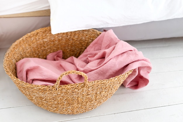 Корзина для белья с розовым полотенцем. интерьер белой стильной комнаты с корзиной для белья
