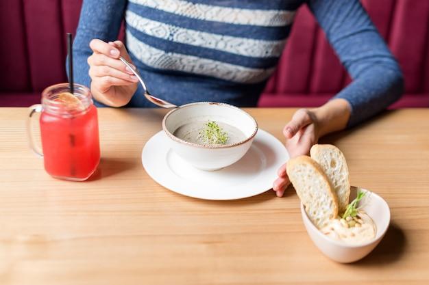 マッシュルームクリームスープのスプーンと白いボウルを保持している女性の作物。