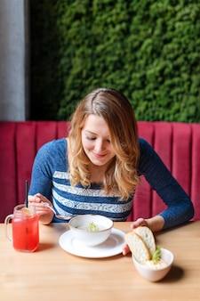 スプーンとキノコのクリームスープの白いボウルを保持している女性