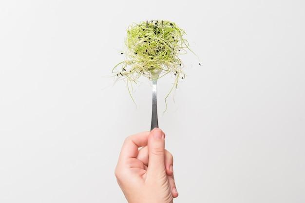 フォークにマイクログリーンを持つ女性の手。