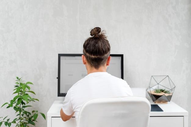 Молодой битник используя компьютер сидя на космосе просторной квартиры. программист набирает код данных, работает над проектом в компании по разработке программного обеспечения.