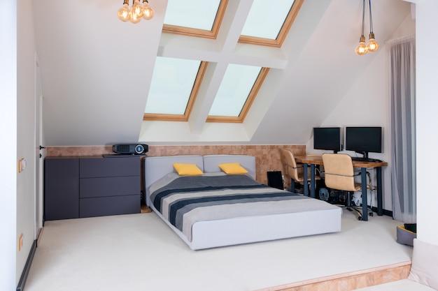 モダンなベッドルームに黄色とグレーの寝具を備えたキングサイズのベッド。快適なベッドと職場のスタイリッシュな部屋のインテリア。