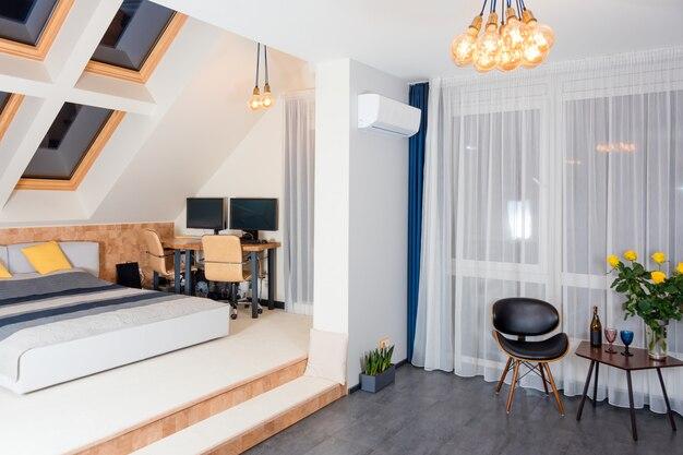 モダンなベッドルームに黄色とグレーの寝具を備えたキングサイズのベッド。