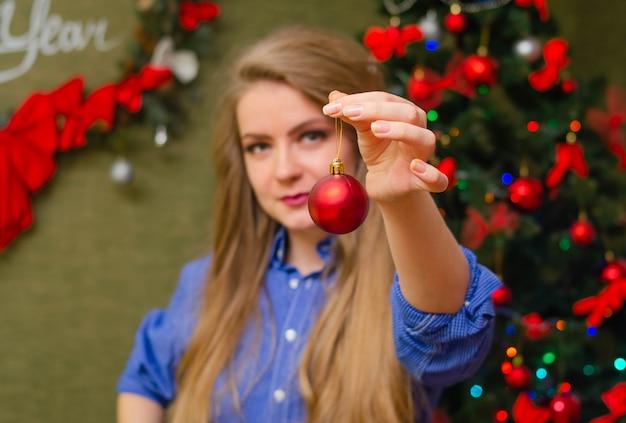 真っ赤な唇、新年のツリーに対してブロンドの長い髪を持つ女性の肖像画。青い男性のシャツの若い女性。彼の前でクリスマスボールの飾りを持っています。ボールを食べる