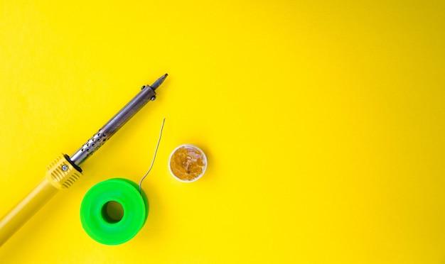 黄色のテーブルにはんだごて、錫、ロジン。男性の手ではんだごて。電気機器の修理、無線工学。はんだワイヤー、接点。